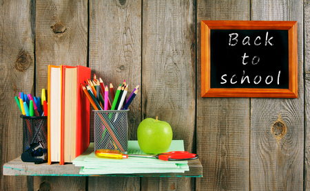 Back to school. School accessories on a wooden shelf. A wooden background. photo