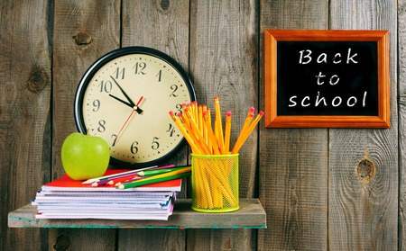 back in an hour: Back to school. Watches and school tools on a wooden shelf.