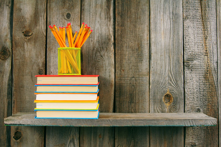 Books and pencils on a wooden shelf. photo