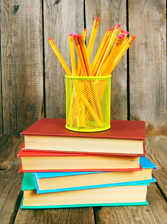 Books and pencils. On a wooden background. photo