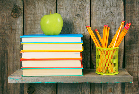 Apple, pencils and books on a wooden shelf. On a wooden background. photo