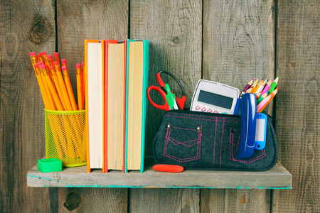 Books and school tools on a wooden shelf. photo