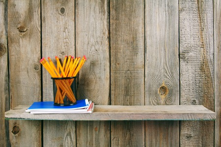 fine tip: Pencils and writing-books on a wooden shelf.