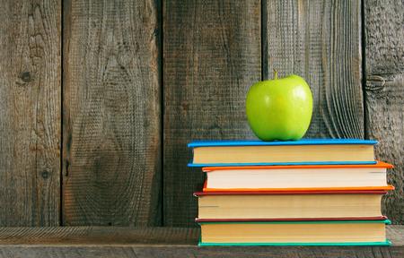 Multi-coloured books and green apple . photo