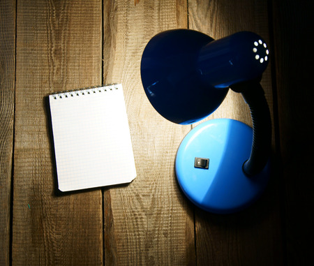 lamplight: Notebook and the fixture. On a wooden background. Stock Photo