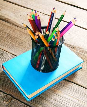 Pencils and book . On wooden background. photo