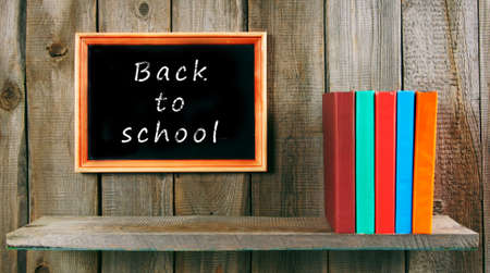 Back to school. Books on wooden background. photo