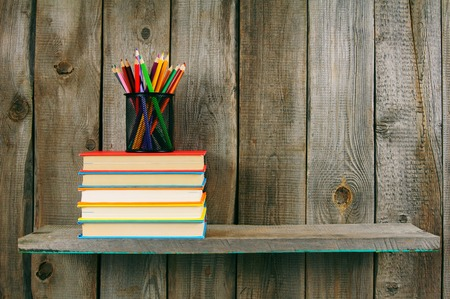 school books: Books and pencils on a wooden shelf.