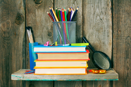 fine tip: Books and school tools on a wooden shelf. Stock Photo