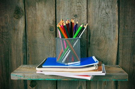 fine tip: Writing-books and school tools on a wooden shelf.