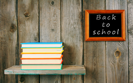 Back to school. Books on wooden shelf and frame. photo