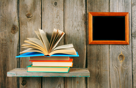 Back to school. The open book on a wooden shelf. Stock Photo