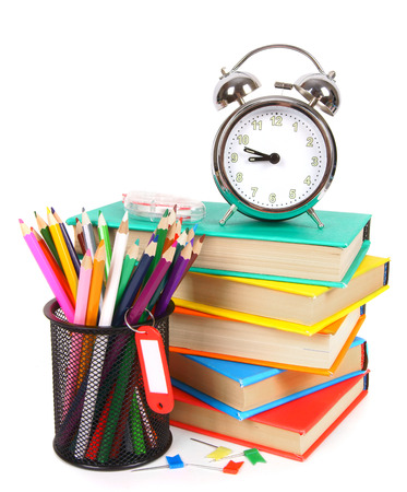 Books, an alarm clock and school tools. photo