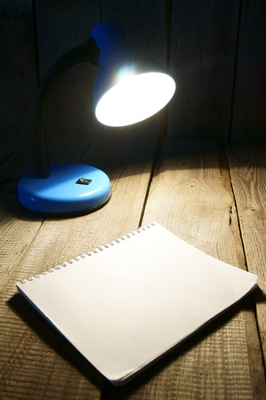 lamplight: Notebook and the fixture. On wooden background. Stock Photo