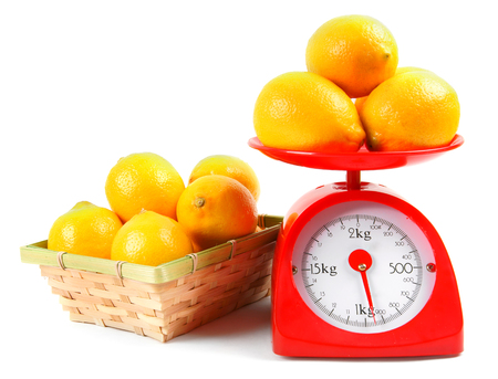 red gram: Lemons on scales and in a basket. Stock Photo