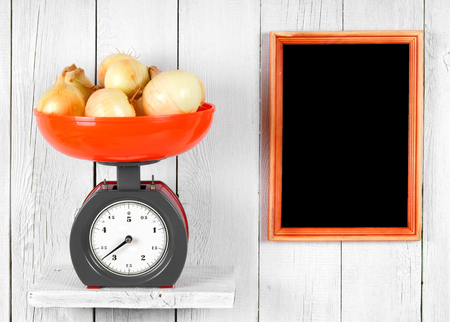 Onions on scales on a wooden shelf. A framework on a wooden background. photo
