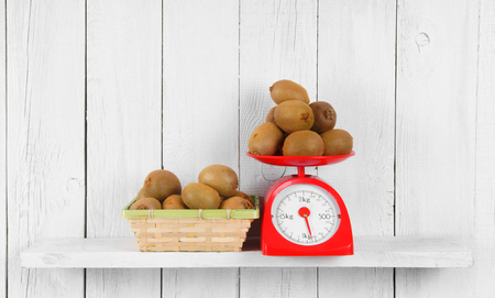 Kiwi on scales and in a basket on a wooden shelf. photo