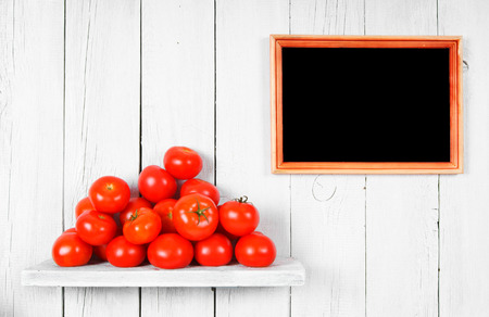Tomatoes on a wooden shelf. A framework on a wooden background. photo