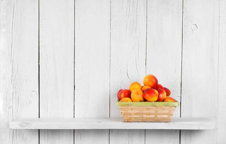 verano: Albaricoques en una cesta en un estante de madera.
