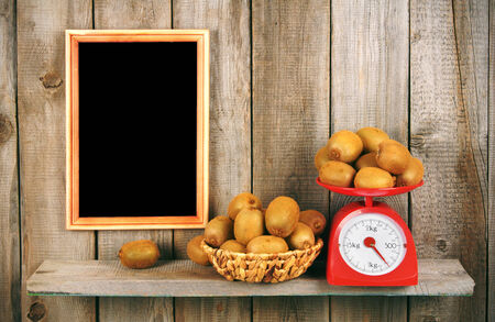 Kiwi on scales and in a basket on a wooden shelf. A framework on a wooden background. photo