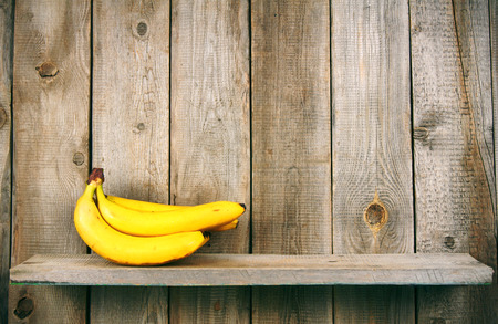 banana peel: Fresh bananas on wooden shelf. Stock Photo