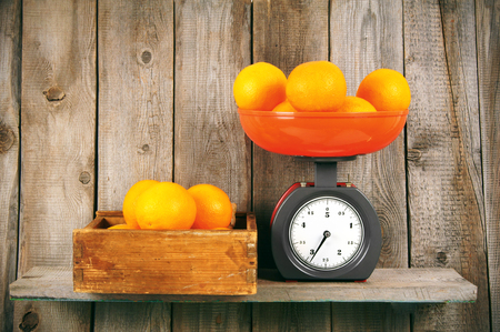 Oranges on scales and in box photo