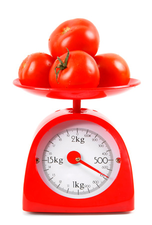 weighing scale: Tomatoes on scales. On white background.