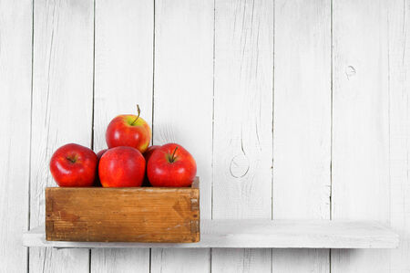 Apples in a box on wooden shelf. photo