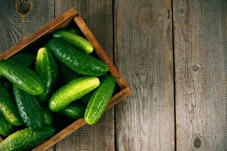 Cucumbers in a box on wooden background. Foto de archivo