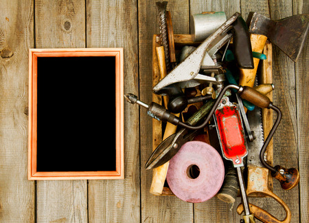 emery: Frame with old tools (drill, mallet, saw and others) in box on wooden background. Stock Photo