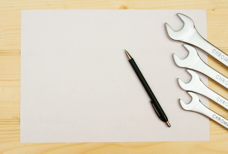 paper with the working tool on wooden background. photo