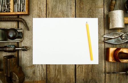 herramientas de construccion: Papel con el lápiz y las herramientas de trabajo de la vendimia en el fondo de madera.