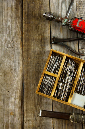 drills: Drills in box, drill, chisel on a wooden background. Stock Photo