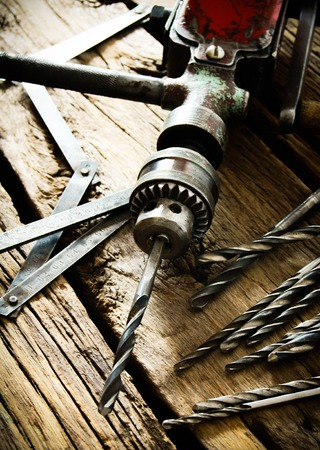 drills: Old drill, ruler and drills on wooden background. Stock Photo