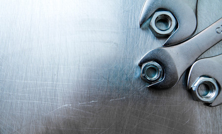 mechanical engineering: Wrenches and nuts on metal background.