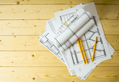 architecture plans: Many drawings for building and pencils on a wooden background.