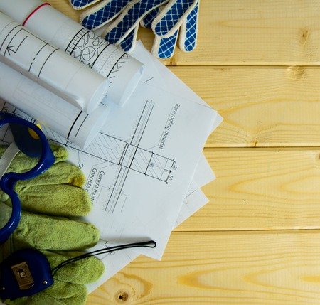 Repair work. Drawings for building, gloves, glasses and others tools on wooden background. photo