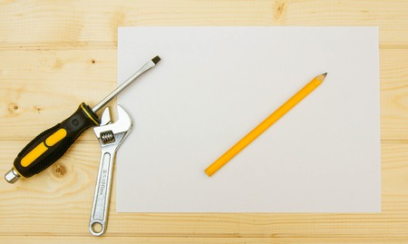 Paper with pencil and working tools on wooden background. photo