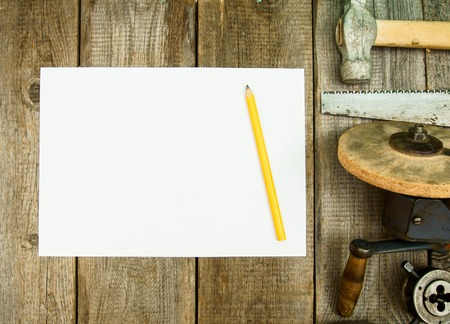 old pencil: Paper with pencil and the vintage working tools on wooden background. Stock Photo