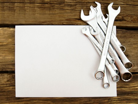 workroom: The Sheet of paper and wrenches on wooden background.