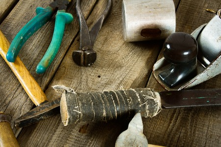 The old working tool. Many old working tools (mallet, plane, hammer and others) on a wooden background. photo