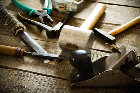 The old working tool. Many old working tools ( hammer, pliers, plane and others) on a wooden background.