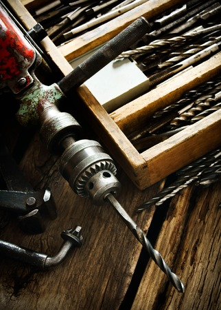 metalworker: Old drill, a box with drills, pliers and ruler on wooden background. Stock Photo