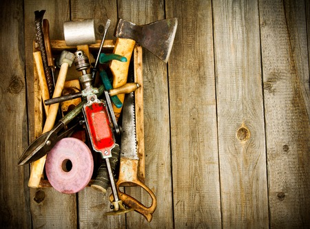 emery: Old working tools (drill, hammer, emery and others) in box on wooden background.