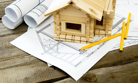 small: Many drawings for building and small house on old wooden background.
