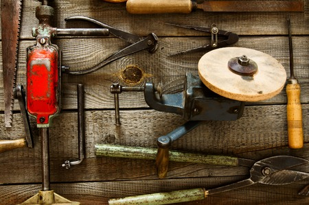 The old working tool. Many old working tools ( plane, saw, pliers and others) on a wooden background. photo
