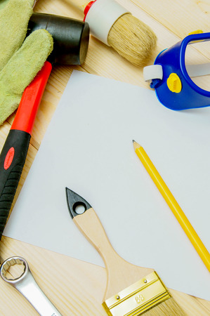 Workng tools. Paper for notes and set of working tools (mallet, brush, gloves and others) on wooden background. photo