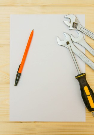 A paper for notes. Paper with a pencil and working tools on a wooden background. photo