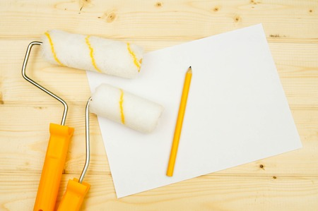 platen: A paper for notes. Paper with a pencil and platen for a paint on wooden background.