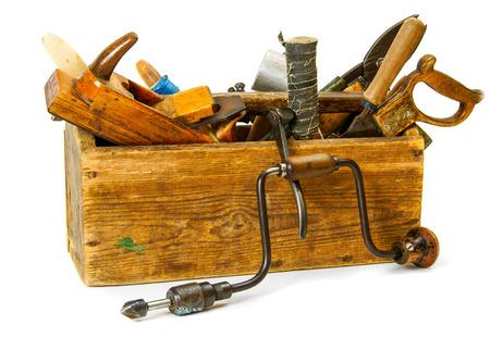 werkzeug: Alte Arbeitsger�te. Arbeitswerkzeuge (Bohrer, Axt, S�ge und andere) in einem alten Kasten auf wei�em Hintergrund. Lizenzfreie Bilder